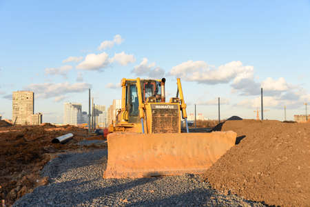 Minsk, Belarus, MARCH 08, 2020: Track-type bulldozer KOMATSU D65EX at construction site. Dozer with bucket for pool excavation and utility trenching. Éditoriale