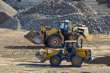 Belarus, JUN 20, 2019: BELAZ-78221 front-end loader and SDLG L953F wheel loader working at mining quarry. Work in open-pit mine.