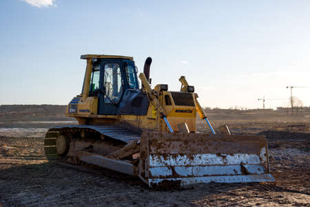 Minsk, Belarus, APR 05, 2020: Track-type bulldozer KOMATSU D65PX at construction site. Dozer with bucket for pool excavation and utility trenching.