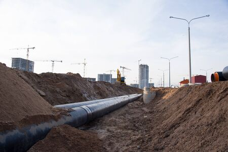 Laying heating pipes in trench at construction site. Installing concrete sewer wells and underground storm systems of sanitary water main. Cold and hot water heating system of the apartments in house Standard-Bild