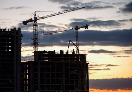 Silhouettes of tower cranes and builders in action on sunset background. Workers during formwork and pouring concrete through a сoncrete pump truck connected to a ready-mixed truck. Concrete pumping