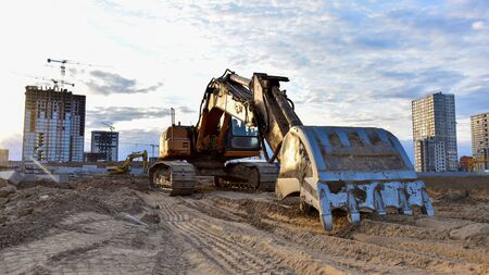 Excavator working at construction site on earthworks. Backhoe digging building foundation. Paving out sewer line. Construction machinery for excavating, loading, lifting and hauling of cargo