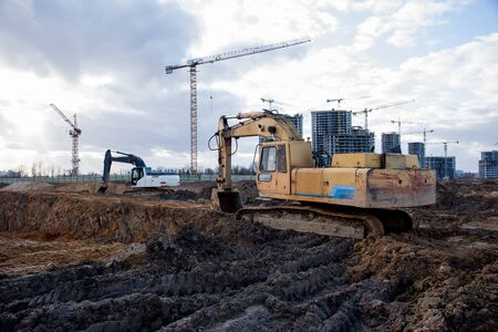 Excavators working at construction site on earthworks. Backhoe digging building foundation. Paving out sewer line. Construction machinery for excavating, loading, lifting and hauling of cargo