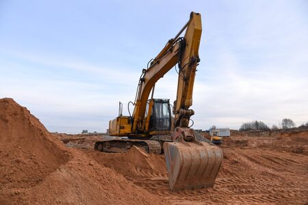 Excavator working at construction site on earthworks. Backhoe on road work digs ground. Paving out sewer line. Construction machinery for excavating, loading, lifting and hauling of cargo Foto de archivo