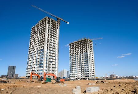 Tower cranes constructing residential buildings. Excavator on earthmoving at construction site. Backhoe dig ground for foundation and laying sewer pipes district heating. Earth-moving heavy equipment on road works