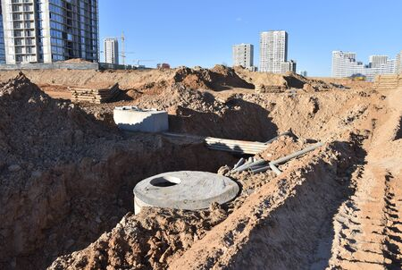 Installation of concrete sewer wells and pipe drainage in the ground. Laying heating pipes in a trench at construction site. Cold and hot water, heating and heating system of apartments in the house