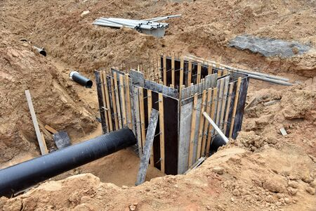 Concrete pile in formwork frame for construct stormwater and underground utilities, pump stations, sewers pipes. Connecting a heating system to a concrete sewer wells structure at construction site.