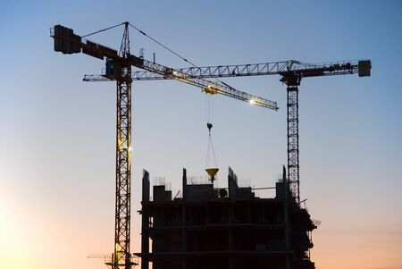 Silhouettes of tower cranes in action on sunset background. Preparing to pour a bucket of concrete into formwork. Ð¡rane lifting cement bucket during construction a multi-storey residential building