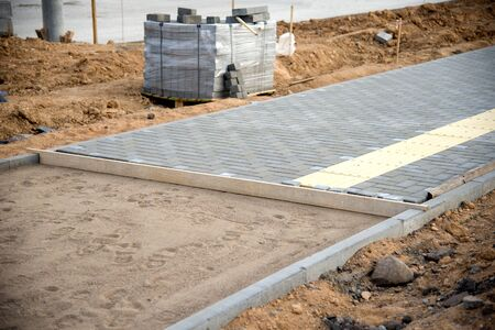 Laying paving slabs and borders at construction site. Process of installing paving bricks in the town pedestrian zone. Screeding the sand for install concrete blocks. Road works on pavement renovation Foto de archivo