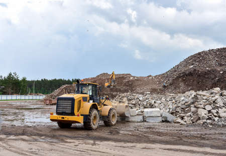 Front end loader and excavator at landfill for disposal of construction waste. Gravel and concrete crushing. Recycling old concrete and asphalt from demolition. Salvaging, removal building materials Imagens