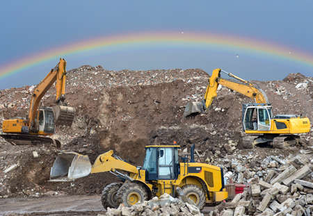 Front end loader and excavators at landfill for disposal of construction waste. Excavator at mining quarry on rainbow background. Recycling concrete and asphalt from demolition. Salvaging and removal