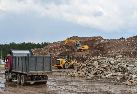 Excavator, dump truck and wheel loader at landfill for disposal of construction waste and concrete crushing. Recycling concrete and asphalt from demolition. Heavy machinery works in mining quarry Imagens