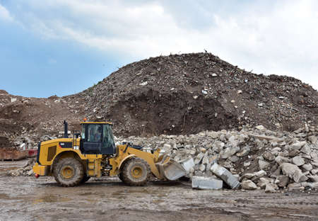 Front end loader at landfill for disposal of construction waste. Backhoe digs gravel and concrete crushing. Recycling old concrete and asphalt from demolition. Salvaging, removal building materials