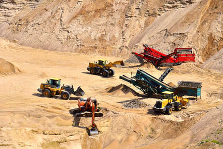Wheel front-end loader loads sand into a dump truck. Heavy machinery in the mining quarry, excavators and trucks. Mobile jaw crusher plant with belt conveyor puts crushing and screening process