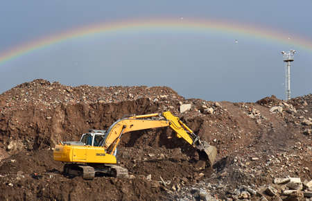 Excavator at landfill on rainbow background in sky. Disposal of construction waste and concrete crushing. Recycling old concrete and asphalt from demolition. Salvaging and removal building material