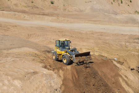 Front end loader has been recovering the landscape around the open pit. Process of restoring land. Mine reclamation occurs once mining sand is completed