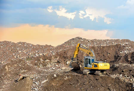 Excavator at landfill for the disposal of construction waste. Backhoe digs gravel and concrete crushing. Recycling old concrete and asphalt from demolition. Salvaging and removal building materials Imagens