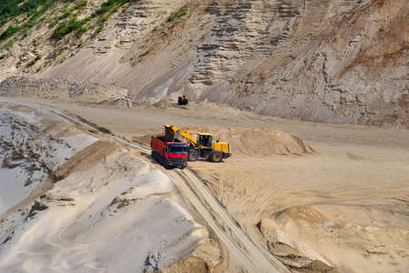 Wheel front-end loader loading sand into heavy dump truck at the opencast mining quarry. Dump truck transports sand in open pit mine. Quarry in which sand and gravel is excavated from the ground.