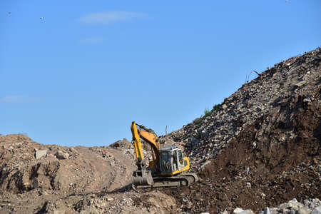 Yellow excavator at landfill for disposal of construction waste. Backhoe dig gravel at mining quarry on blue sky background. Recycling concrete and asphalt from demolition.