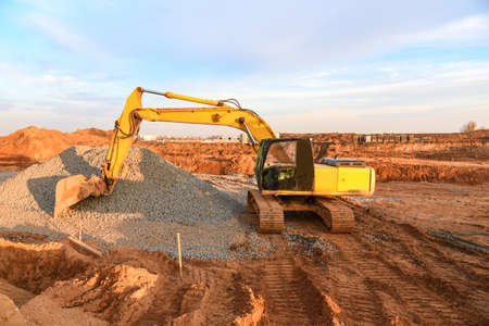 Excavator working on road work at a construction site on sunset background. Screeding gravel and ground for laying asphalt on the new road. Road equipment. Civil Work Contracting, trenching