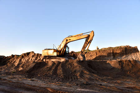 Excavator working on earthmoving. Backhoe digs ground in sand quarry on blue sky background. Construction machinery for excavation, loading, lifting and hauling of cargo on job sites Imagens