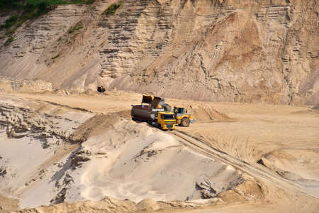 Wheel front-end loader loading sand into heavy dump truck at the opencast mining quarry. Dump truck transports sand in open pit mine. Quarry in which sand and gravel is excavated from the ground. Imagens