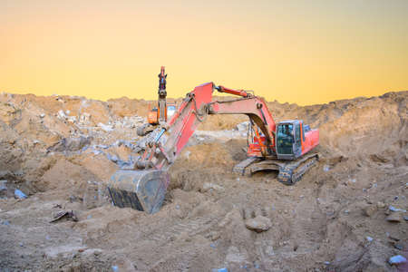 Excavator working on earthmoving at open pit on sunset background. Heavy machinery working in the mining quarry. Digging and excavation operations Imagens