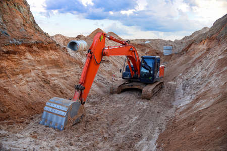 Excavator working at a construction site during laying or replacement of underground storm concrete pipes and sewer wells. Installation of water main, sanitary sewer, storm drain systems in tranch