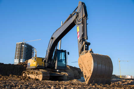 Excavator during earthmoving at construction site on blue sky background. Backhoe digging the ground for the foundation and for laying sewer pipes district heating. Earth-moving heavy equipment Banque d'images
