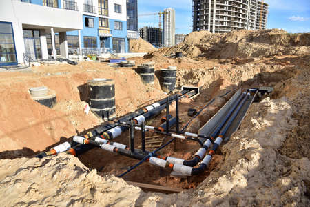 Laying heating pipes in trench at construction site. Installing concrete sewer wells and underground storm systems of sanitary water main. Cold and hot water heating system of the apartments in house Stock fotó