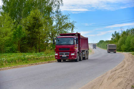 Tipper Dump Truck transported sand from the quarry on driving along highway. Modern Heavy Duty Dump Truck with unloads goods by itself through hydraulic or mechanical lifting