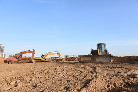 Excavators and dozer digs ground at a construction site for installing sewer storm pipes. Backhoe for digging pipeline ditch. Commercial and Public Civil Work Contracting, trenching, tamps soil