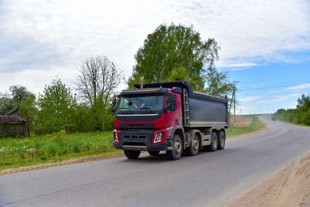 Tipper Dump Truck transported sand from the quarry on driving along highway. Modern Heavy Duty Dump Truck with unloads goods by itself through hydraulic or mechanical lifting Archivio Fotografico
