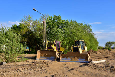 Track-type bulldozers during of large construction jobs at building site. Land clearing, grading, pool excavation, utility trenching, utility trenching and foundation digging. Earth-moving equipment.