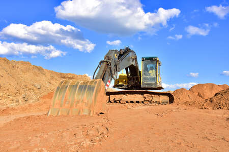 Excavator working on earthmoving at open pit mining on blue sky background. Backhoe digs sand in quarry. Earth-moving heavy equipment and Construction machinery during excavation