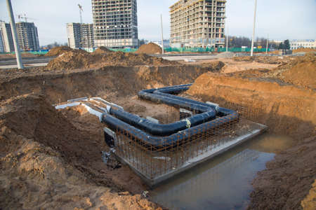 Laying of underground storm sewer pipes in ditch. Installation of water main and sanitary sewer at the construction site. Formwork solutions for reinforced construction and framed superstructure. Foto de archivo