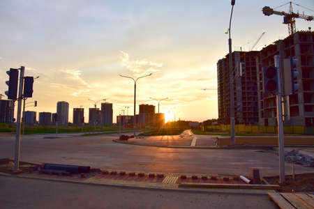 View on the large construction site with tower cranes and buildings on sunset background. Roadwork, laying curbs and paving slabs. Pedestrian crossing, road and traffic light 版權商用圖片