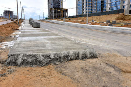 Road works activity at construction site. Construction and development projects on roads in city. Road concreting. Asphalt pavement is layered over concrete pavement 版權商用圖片