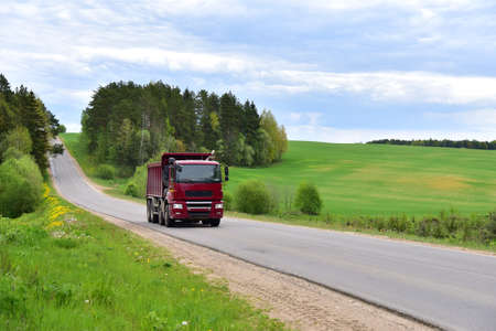 Tipper Dump Truck transported sand from the quarry on driving along highway. Modern Heavy Duty Dump Truck with unloads goods by itself through hydraulic or mechanical lifting Standard-Bild