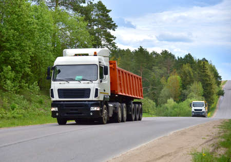 Truck with tipper semi trailer transported sand from the quarry on driving along highway. Modern Dump Semi-Trailer Rear Tipper Truck Trailer