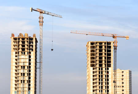Preparing to pour a bucket of concrete into formwork.Tower crane lifting cement bucket during construction a multi-storey residential building. Construction cranes and builders in action