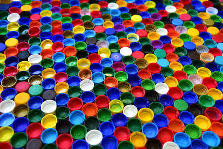 Plastic bottle caps background. Waste cap material is recyclable. Plastic lids from HDPE for recycle. Recycling plastic bottle caps.