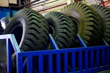 Warehouse with tires for trucks at an industrial plant for the production of cars. The protector of a large rubber wheel. Rubber tire from the tipper. Mounting