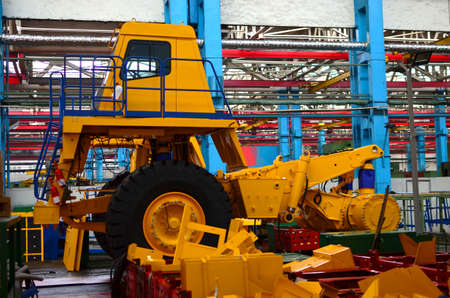 Production process of heavy mining trucks at the factory. Dump truck on the Industrial conveyor in the workshop of an automobile plant. Manufacturer of haulage and earthmoving equipment, haul trucks Foto de archivo