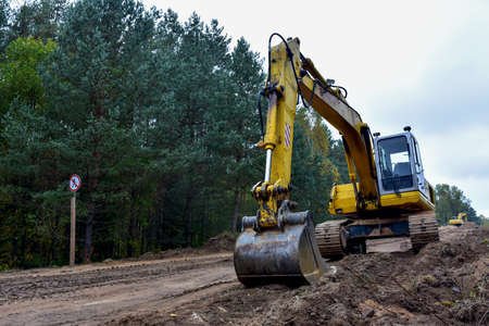 Excavator during construction new road in forest area. Yellow backhoe at groundwork. Earth-moving equipment fort road work, grading, pool excavation, utility trenching