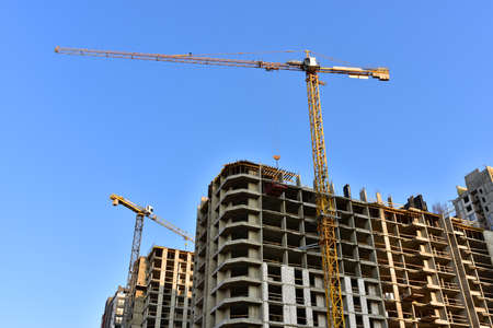 Tower cranes working at construction site on blue sky background. Construction process of the new modern residential buildings Stock Photo
