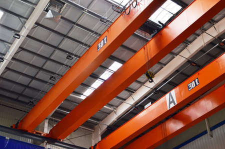 Bridge lifting Crane Hook with electric engines on the background of the industrial workshop production plant. The concept of a heavy manufacturing process at an industrial factory - Image 免版税图像