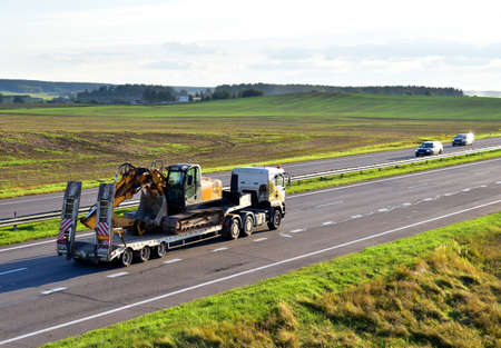 Trailer truck with long platform transport the Excavator on highway. Earth mover backhoe on heavy duty flatbed vehicle for transported. Long Haul and Shipping Services. Loading on Low Bed Trailer