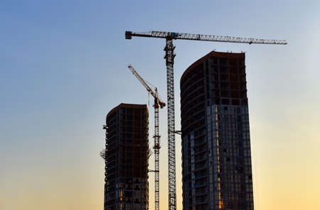 Tower cranes working at construction site on sunset background. Construction process of the new modern residential buildings. Construction roads and streets in city. Soft focus