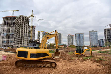 Excavator and mini excavator during excavation and road construction works at construction site. Backhoe on foundation work. Tower cranes on constructing residential building and modern skyscrapers Standard-Bild